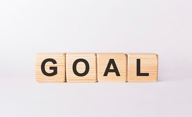 Słowo goal wykonane z drewnianych klocków na białym tle