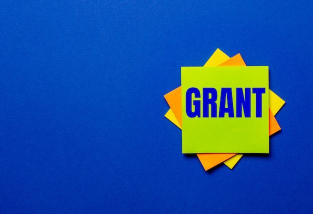 Słowo grant jest zapisane na jasnych naklejkach na niebieskiej ścianie