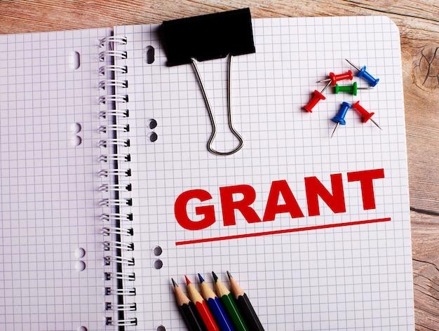 Słowo grant jest zapisane w zeszycie obok wielokolorowych ołówków i guzików na drewnianym stole.