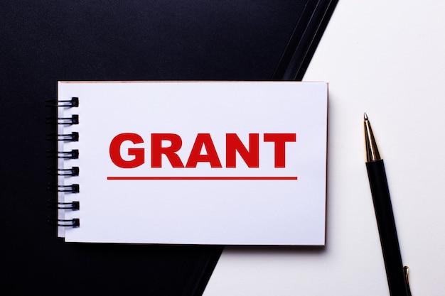 Słowo grant napisane na czerwono na czarno-białej powierzchni w pobliżu długopisu