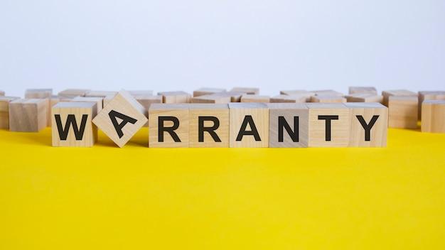 Słowo gwarancyjne składa się z drewnianych klocków leżących na żółtym stole, koncepcja