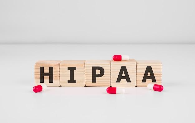 Słowo hipaa wykonane z drewnianych klocków z czerwonymi pigułkami, koncepcja medyczna.