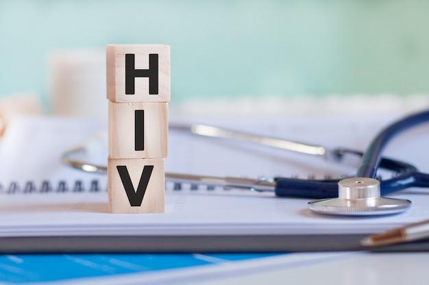 Słowo hiv jest napisane na drewnianych kostkach w pobliżu stetoskopu na tle papieru. hiv - skrót od ludzkiego wirusa niedoboru odporności. pojęcie medyczne.