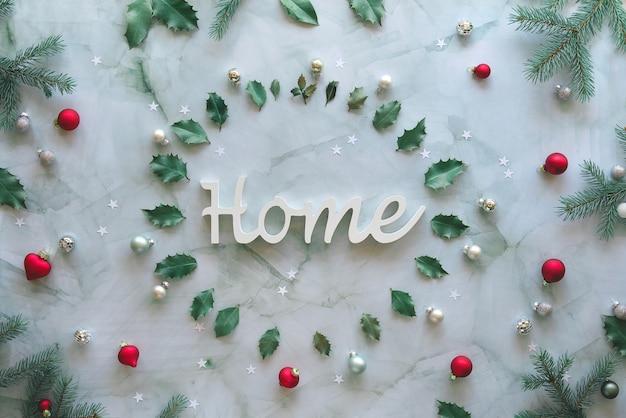 Słowo home w marmurowym kole. boże narodzenie tło z naturalnymi gałązkami jodły, liśćmi ostrokrzewu i bombkami szklanymi. świąteczne mieszkanie leżało w kolorze szarym, zielonym, czerwonym.
