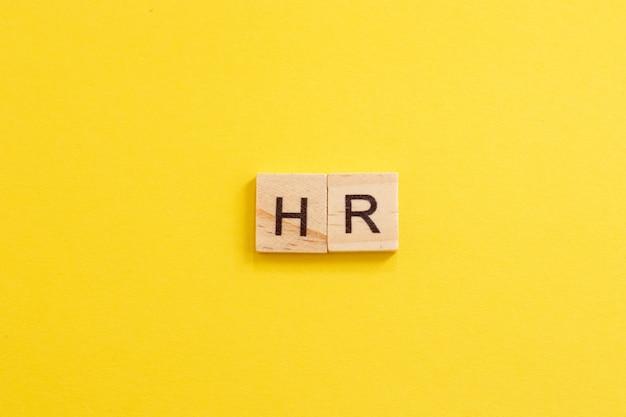 Słowo hr wykonane z drewnianych liter na żółtym tle. zasoby ludzkie. koncepcja hr. nowy pracownik