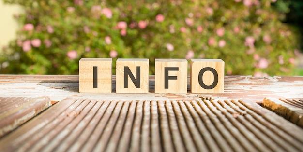 Słowo info jest napisane na drewnianych kostkach. klocki są umieszczone na starej drewnianej desce oświetlonej słońcem. w tle jasno kwitnący krzew