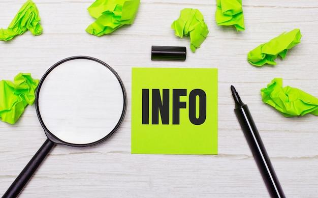 Słowo info zapisane na zielonej karteczce obok lupy i czarnego markera na drewnianym stole