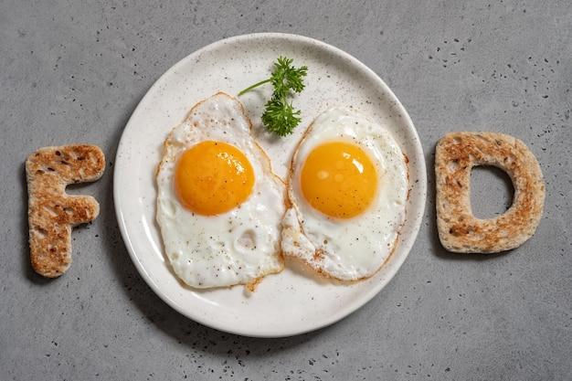 Słowo jedzenie pisane z listami tostów i smażonymi jajkami