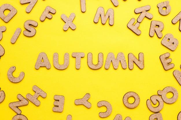 Słowo jesień wśród drewnianych liter na żółtej powierzchni.
