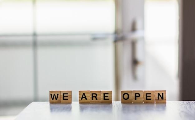 Słowo jesteśmy otwarci zrobione z drewnianych kostek na tle otwartych drzwi koniec kwarantanny kawiarnia osiedlowego sklepu witającego gości po wybuchu koronawirusa i zamknięciu ludzi