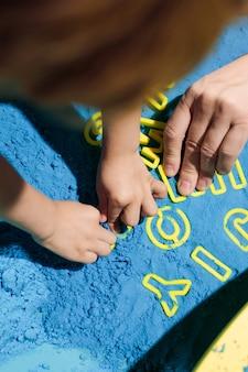 Słowo joy, ułożone w kinetycznym piasku przez ręce dzieci. terapia sztuką. łagodzenie stresu i napięcia. wrażenia dotykowe. nauka poprzez grę. rozwój umiejętności motorycznych.