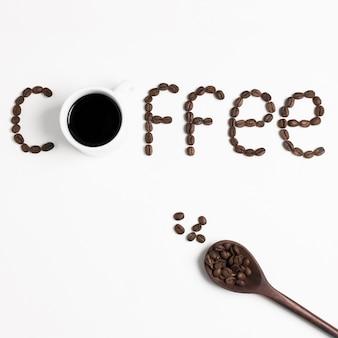 """Słowo """"kawa"""" zapisane z palonych ziaren kawy i łyżką"""