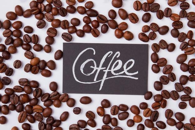 Słowo kawy i prażone ziarna rozrzucone dookoła