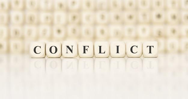 Słowo konflikt wykonane z drewnianych klocków