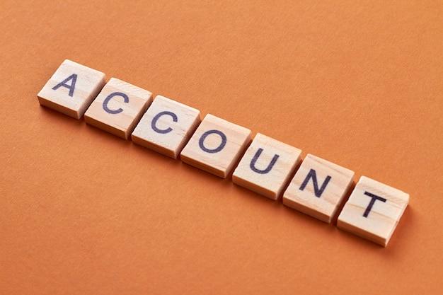 Słowo konta na drewnianych kostkach. słowo napisane literami na drewnianych kostkach. na białym tle na pomarańczowym tle.