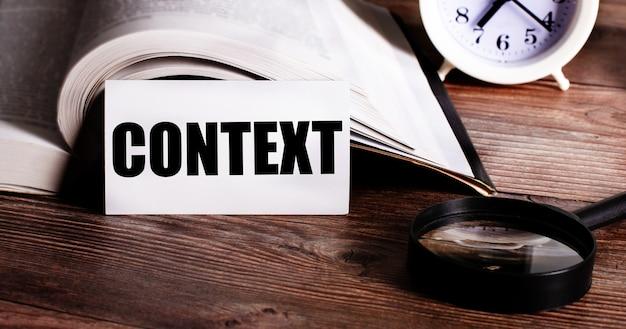 Słowo kontekst zapisane na białej karcie obok otwartej książki, budzika i lupy