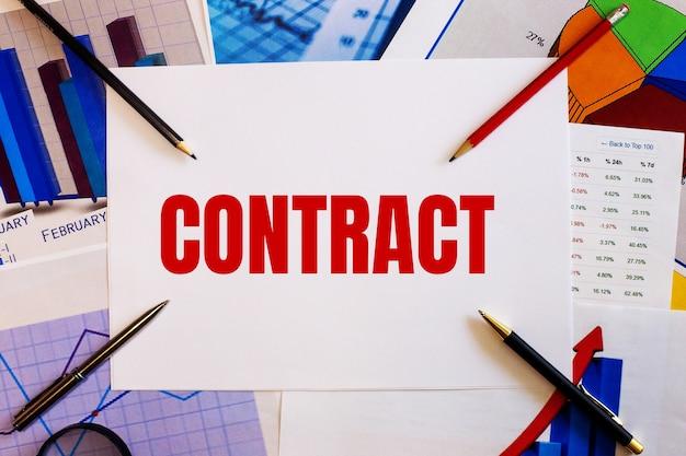 Słowo kontrakt jest napisane na białej ścianie obok kolorowych wykresów, długopisów i ołówków. pomysł na biznes