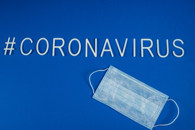 Słowo koronawirus ułożone białymi literami. maska ochrony dróg oddechowych obok słowa koronawirus. nowości w sieciach społecznościowych. hashtag. leżał płasko, lato