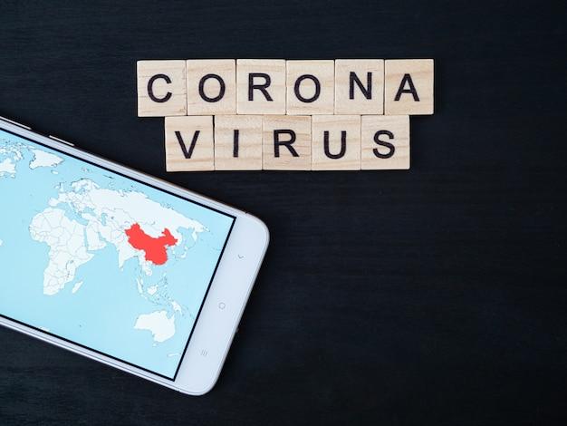 Słowo koronawirusa wykonane z bloku drewna i mapy świata na ekranie smartfona. tekst koronawirusa na dramatycznej atmosferze czarny drewniany stół. widok z góry koncepcja koronawirusa, miejsce