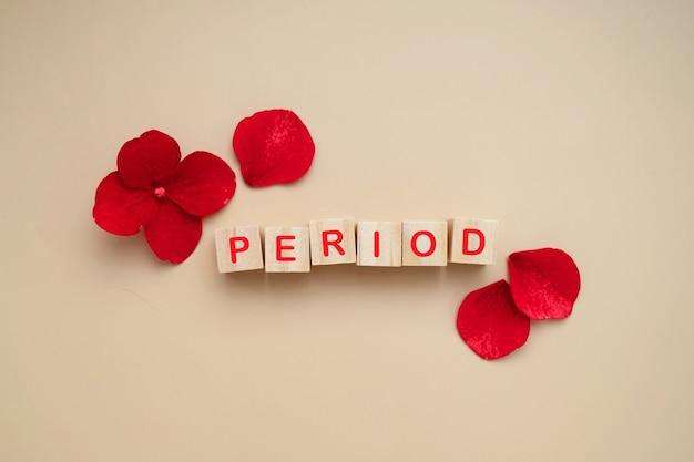 Słowo kropki na drewnianym klocku, litery z czerwonymi kwiatami. streszczenie miesiączki i pojęcie zdrowia kobiety. widok z góry.