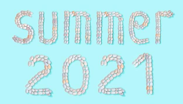 Słowo lato i liczba 2021 ułożone z małych podobnych naturalnych muszelek