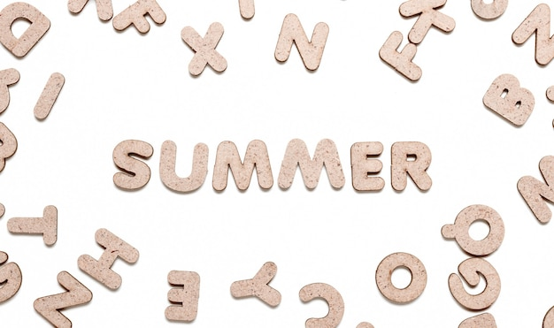 Słowo lato wśród drewnianych liter na białym tle.