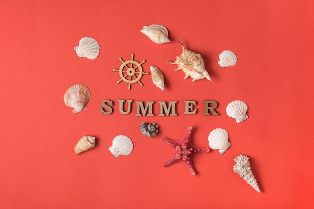 Słowo lato z drewnianych liter. muszle, rozgwiazdy i kierownica. żywe tło koralowe. leżał płasko. koncepcja morska