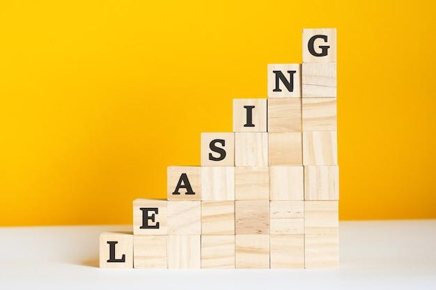 Słowo leasing jest zapisane na drewnianych kostkach. koncepcja hierarchii korporacyjnej i marketing wielopoziomowy.