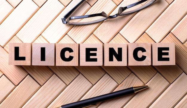 Słowo licencja jest zapisane na drewnianych kostkach na drewnianej ścianie obok długopisu i okularów.