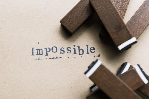 Słowo litery alfabetu niemożliwe od czcionki znaczków na papierze dla niemożliwego tła koncepcji