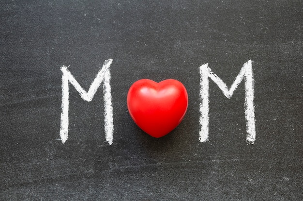 Słowo mama odręcznie na tablicy szkolnej z czerwonym sercem jako litera o