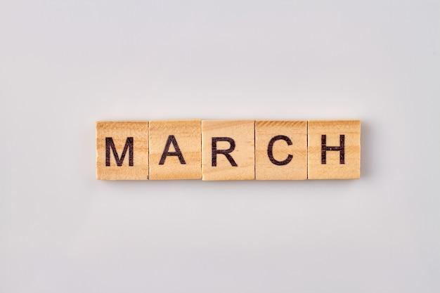 Słowo marca napisane na klockach drewnianych. na białym tle