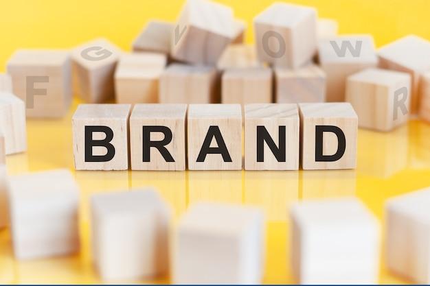 Słowo marka zapisane jest na drewnianej konstrukcji z kostki, koncepcja finansowa.