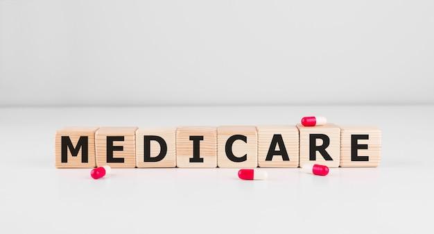 Słowo medicare wykonane z drewna klocki z czerwonymi pigułkami, koncepcja medyczna.