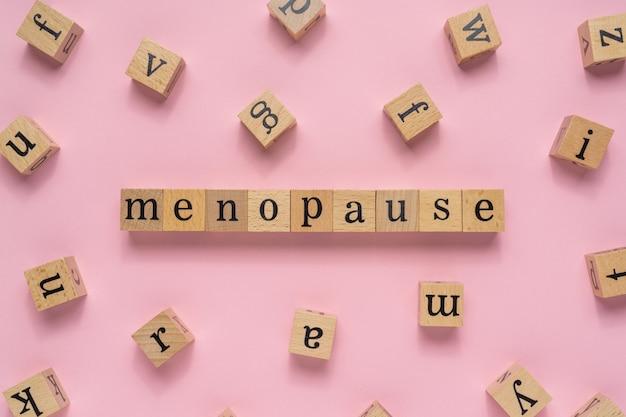 Słowo menopauza na drewnianym bloku.