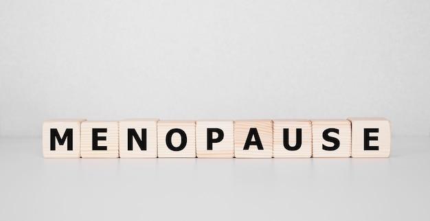 Słowo menopauzy napisane na bloku drewna. tekst menopauzy na stole, koncepcja.
