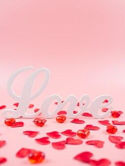 Słowo miłość i czerwone serca na różowym tle. walentynki