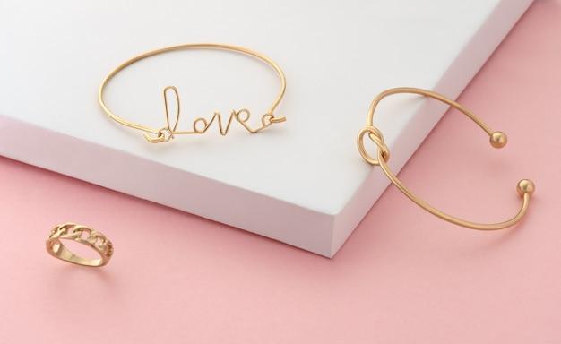 Słowo miłość i kształt węzła złote bransoletki i pierścionek na różowo i białym tle