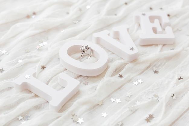 Słowo miłość na białym materiale z diamentowym pierścionkiem zaręczynowym. dobry na kartki walentynkowe.