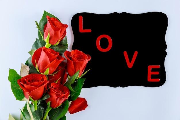 Słowo miłość na czarnej tablicy i bukiet pięknych czerwonych róż. walentynki lub dzień matki.