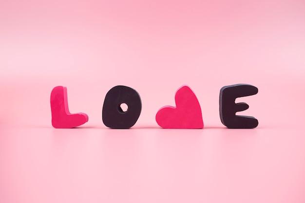 Słowo miłość na różowym tle. walentynki