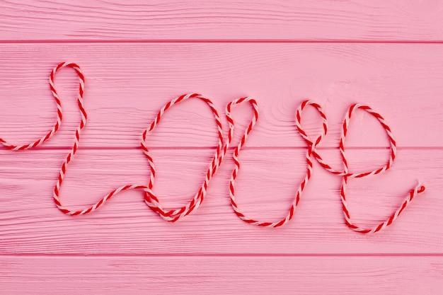 Słowo miłość napisane wełnianą nicią.