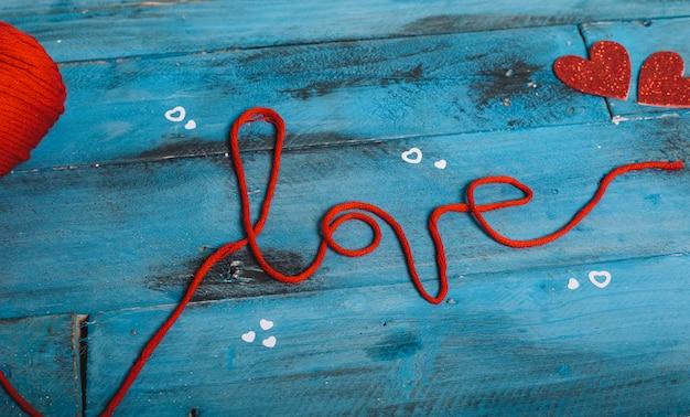 """Słowo """"miłość"""" nićmi z czerwonej wełny i dwoma sercami"""