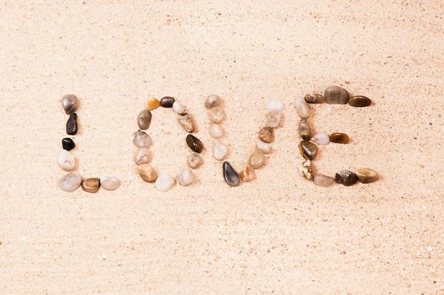 Słowo miłość pisać z otoczakami na piasku plaża