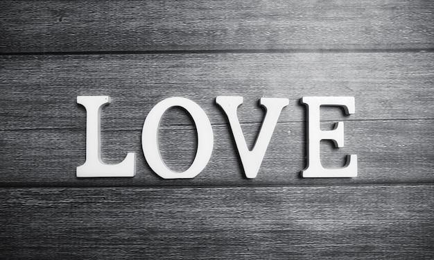 Słowo miłość składa się z białych drewnianych liter na drewnianym tle