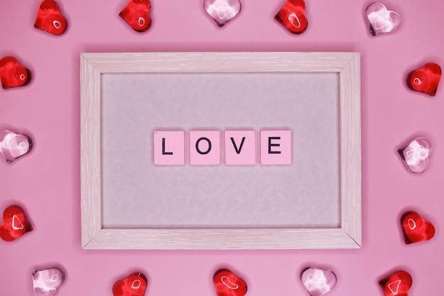 Słowo miłość w ramce, z postaciami serc. walentynki