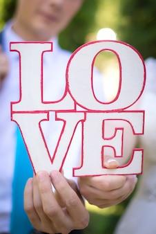 Słowo miłość w rękach kochanków