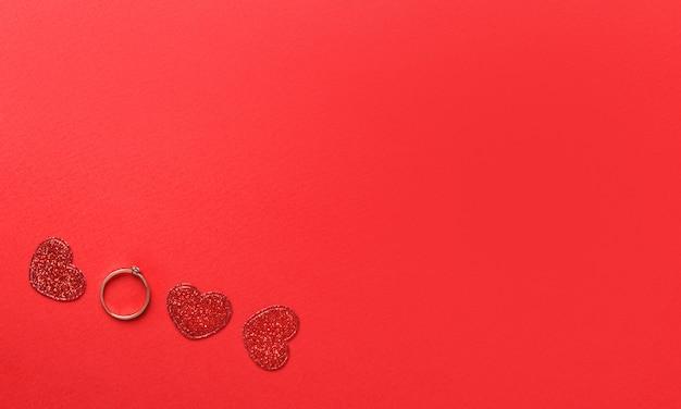 Słowo miłość wykonane z czerwonych brokatowych serc i złotego pierścienia na czerwonej ścianie