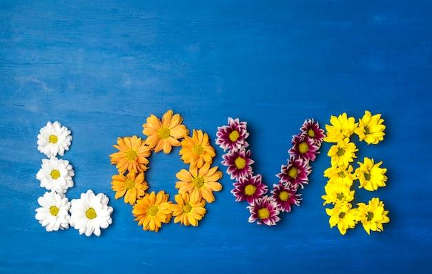 Słowo miłość wykonane z kwiatów na niebieskim tle