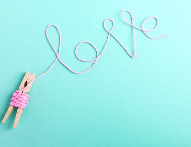 Słowo miłość wykonane z różowej rolki wełny
